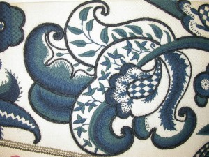 A stylised leaf in rich blues with many decorative filling stitches.
